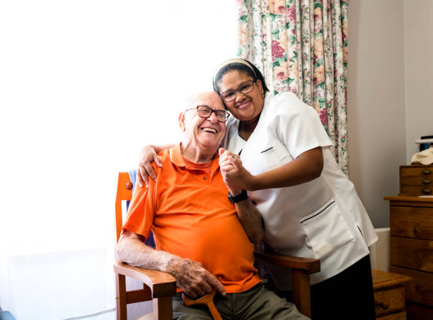 portrait of a smiling senior man and nurse embracing - outpatient stock pictures, royalty-free photos & images