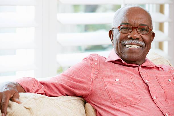 portrait of a smiling senior man at home - sadece yaşlı bir adam stok fotoğraflar ve resimler