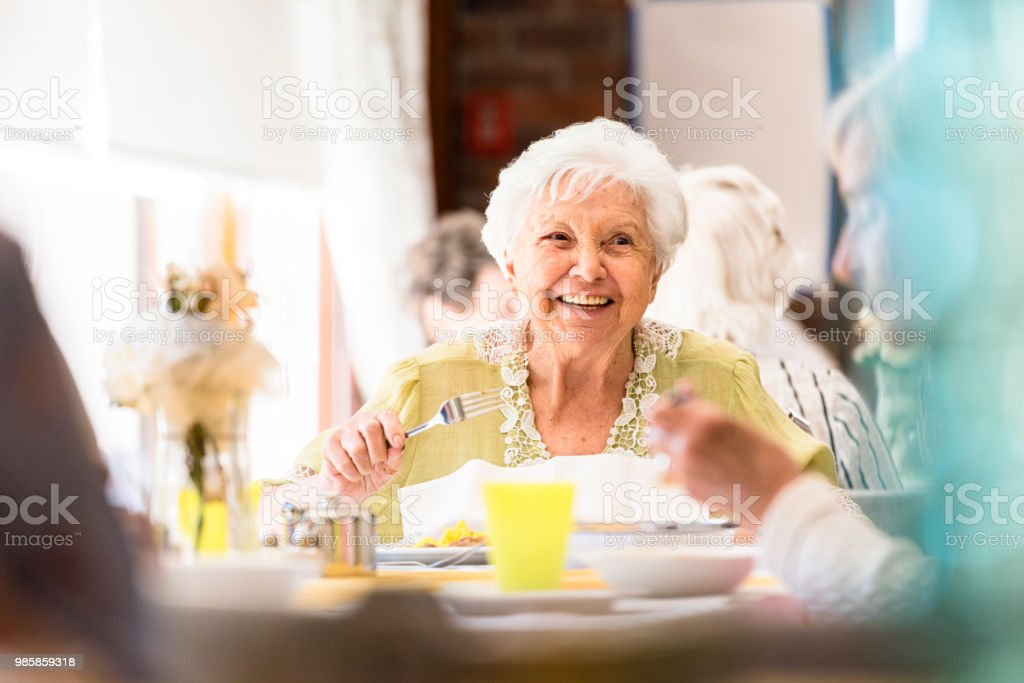Portrait of a smiling senior woman having lunch with friends stock photo