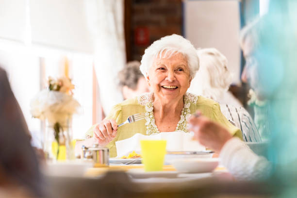 Portrait of a smiling senior woman having lunch with friends Portrait photo of a senior woman having lunch retirement community stock pictures, royalty-free photos & images