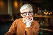 Portrait of a beautiful smiling senior woman with short hair. She is looking to camera