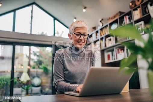 Portrait of a smiling senior woman using laptop.
