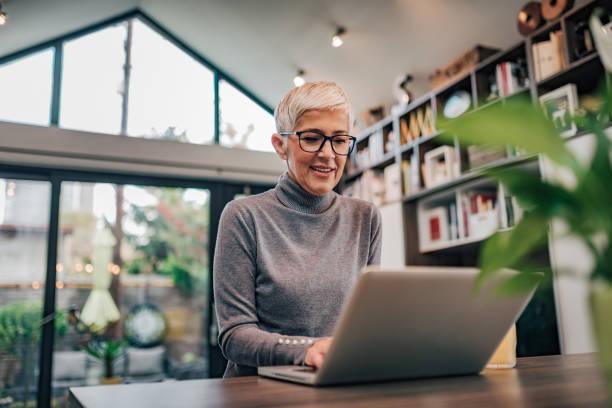 Retrato de una mujer mayor sonriente usando computadora portátil. - foto de stock