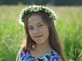 Portrait of a smiling teenager girl among meadow flowers. Happy child in nature