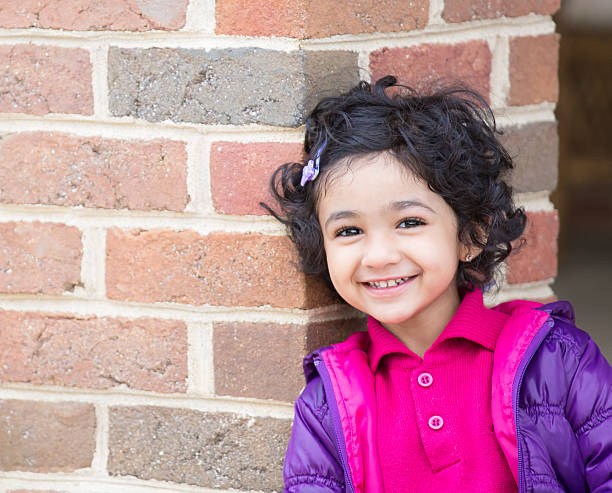 Portrait of a smiling toddler girl next to a brick wall  stock photo