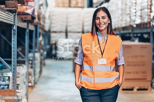 Smiling young woman with reflective clothing in a large warehouse