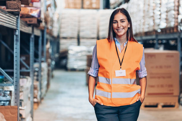 Portrait of a smiling warehouse manager Smiling young woman with reflective clothing in a large warehouse reflective clothing stock pictures, royalty-free photos & images