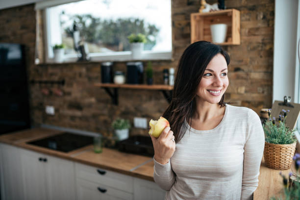 Portrait of a smiling woman eating apple and looking through window while standing in the kitchen. stock photo