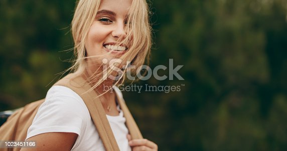 Close up of woman on a holiday walking in a park wearing a bag. Portrait of a smiling woman with brown hair flying over her face.