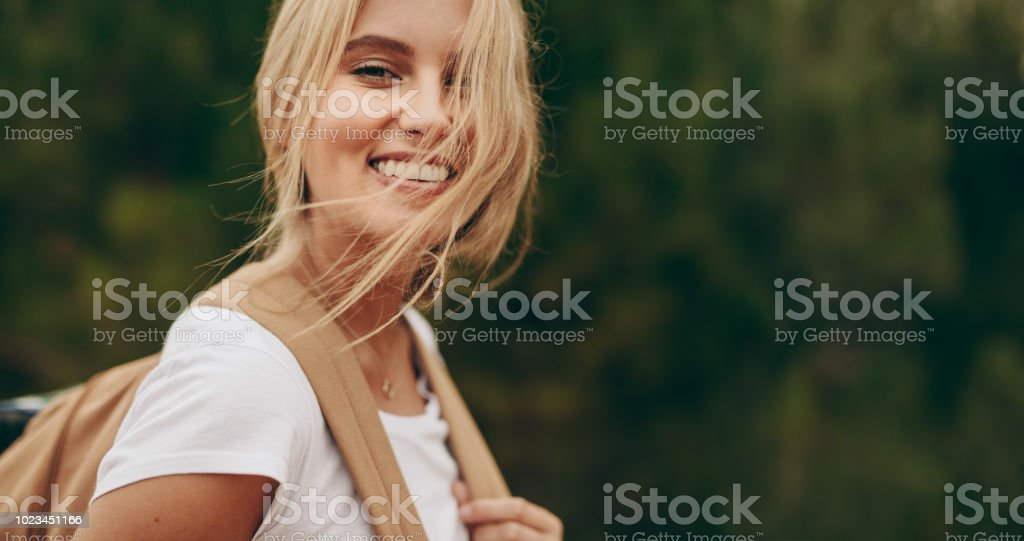 Portrait of a smiling woman explorer wearing a backpack stock photo