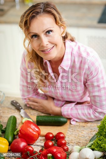 istock portrait of a smiling woman in the kitchen 962264280