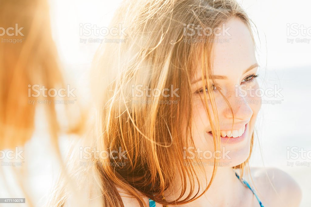 Portrait of a smiling woman on the beach at sunset stock photo
