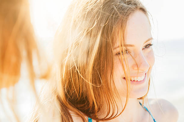 portrait of a smiling woman on the beach at sunset - 2015 stock pictures, royalty-free photos & images