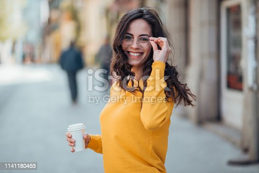 Portrait of a smiling woman walking in the city with take-away drink on a spring day.