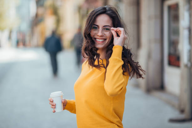 Portrait of a smiling woman walking in the city with take-away drink on a spring day. stock photo