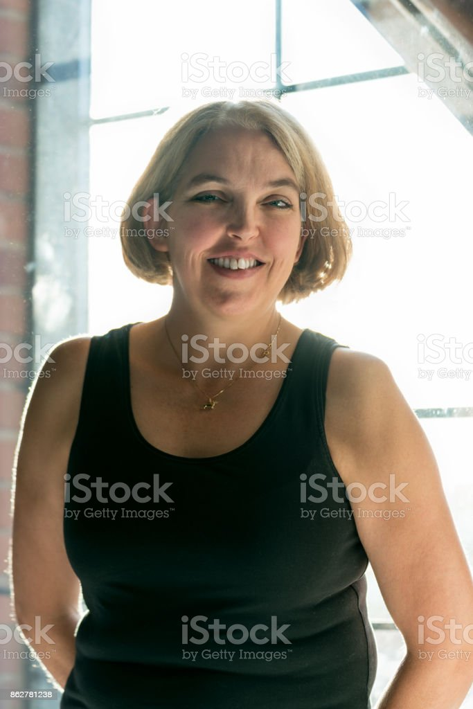 Portrait of a smiling woman wearing a black tank top standing in front of a big bright window. stock photo