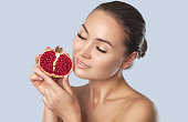 Portrait of a smiling woman with clean skin holds ripe pomegranate near the face. Cosmetology skin care and makeup concept.