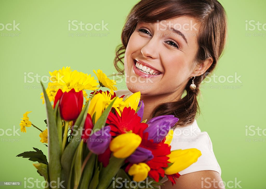 Portrait of a smiling woman with colorful flowers royalty-free stock photo