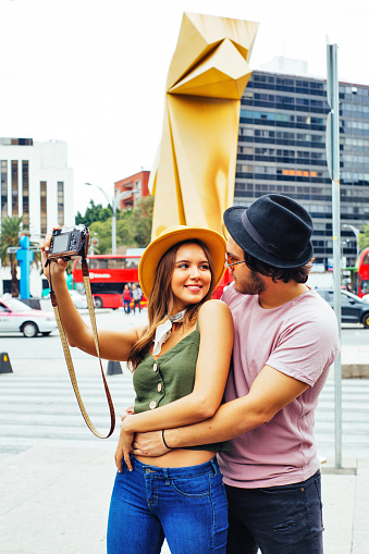 Portrait of a smiling young couple having fun taking selfie  looking at each other on street of Mexico City center with caballito de la loteria, in background