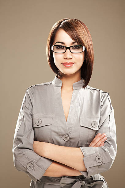 Portrait of a smiling young ethnic business woman in spectacles Close-up portrait of a smiling young ethnic business woman in black spectacles. Vertical shot. smirking stock pictures, royalty-free photos & images