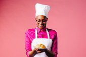Portrait of a smiling young female chef holding a plate with a freshly made croissant