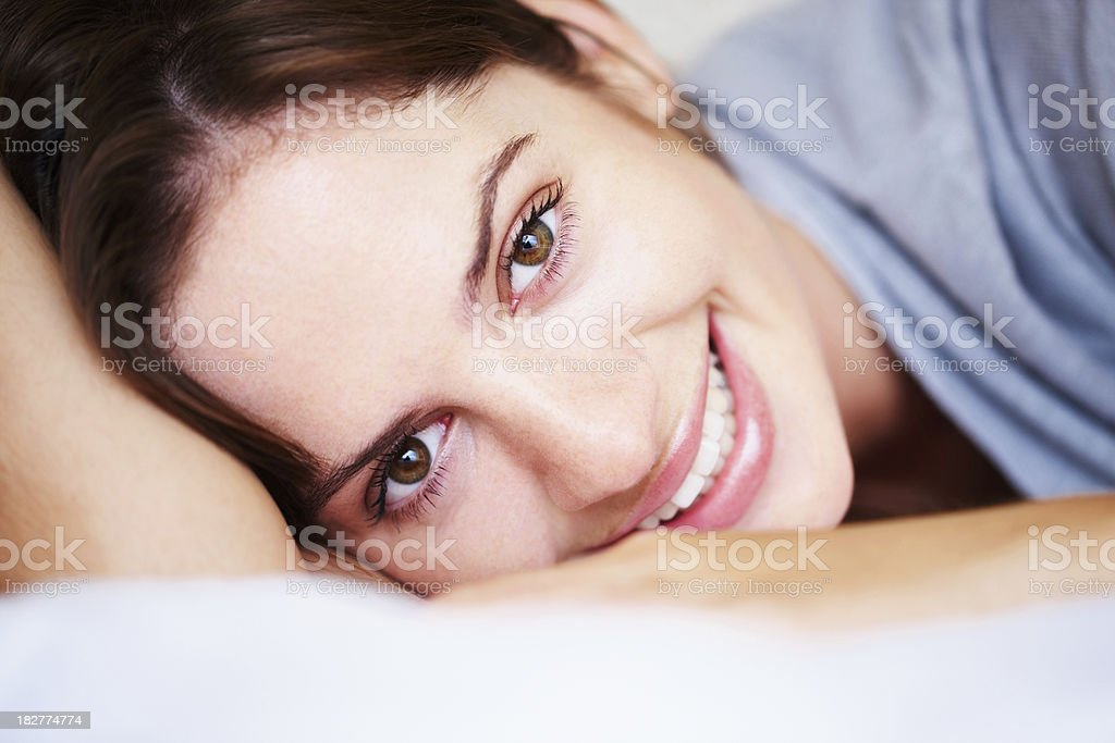 Portrait of a smiling young female lying on bed royalty-free stock photo