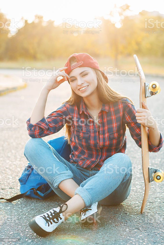 Portrait of a fun smiling young girl with skateboard and backpack at...