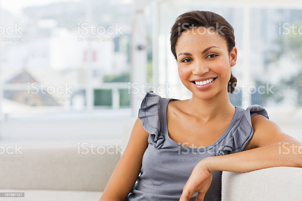 Portrait of a smiling young lady sitting on couch royalty-free stock photo