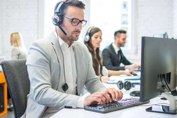 Portrait of a smiling young man with headset using computer in the office stock photo