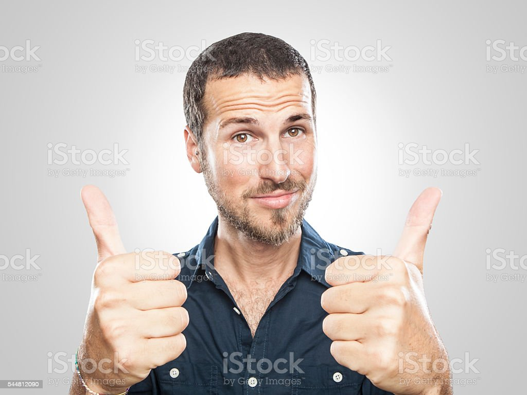 portrait of a smiling young man with thumbs up stock photo