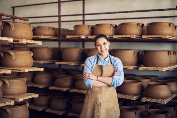 retrato de uma mulher nova de sorriso em um estúdio cerâmico. - cerâmica artesanato - fotografias e filmes do acervo