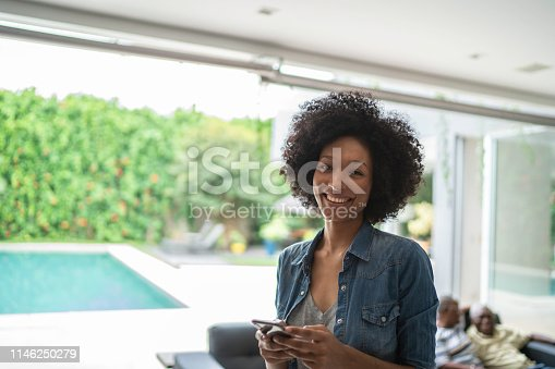 istock Portrait of a smiling young woman using cellphone 1146250279