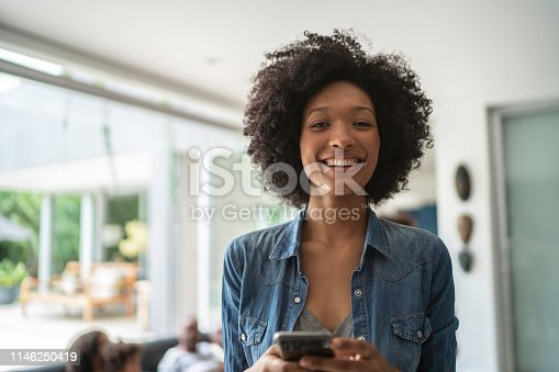 istock Portrait of a smiling young woman using cellphone 1146250419