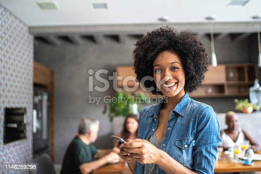 istock Portrait of a smiling young woman using cellphone 1146259298