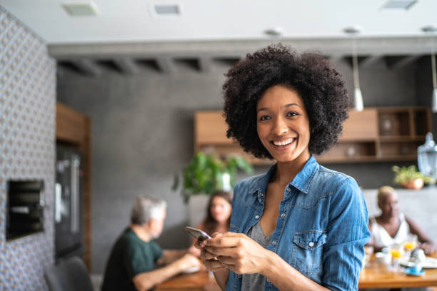 Portrait of a smiling young woman using cellphone Portrait of a smiling young woman using cellphone brazilian ethnicity stock pictures, royalty-free photos & images