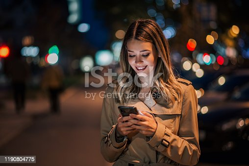 istock Portrait of a smiling young woman using smart phone at night. 1190804775