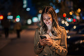 Portrait of a smiling young woman using smart phone at night.