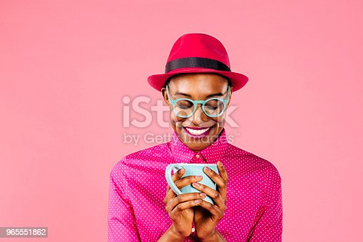 Portrait of a smiling young woman with hat and glasses holding coffee mug, looking down, isolated on pink studio background