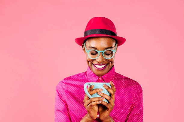 porträt einer lächelnden jungen frau mit hut und brille hält kaffeetasse - gesichtertassen stock-fotos und bilder