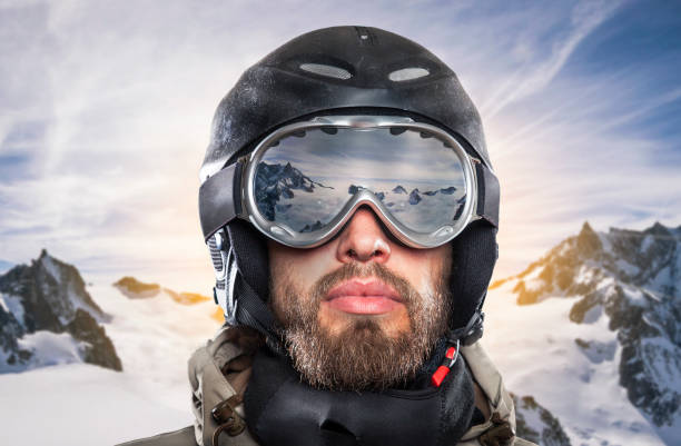portrait of a snowboarder in wintry environment portrait of a snowboarder with helmet and goggles in front of sunrise in wintry mountains landscape ski goggles stock pictures, royalty-free photos & images