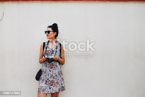 Portrait of a young brunette woman. She is enjoying the walk and exploring the city, wearing a casual but fashionable dress, taking a short break, leaning against the wall in Singapore street. She is holding an analog film camera, or maybe a new mirrorless in a nice retro body.