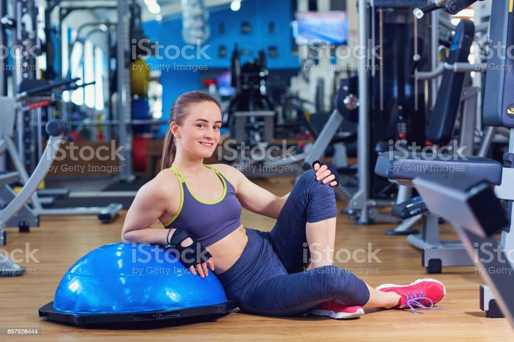 Portrait of a sports girl sitting on  floor in the gym stock photo