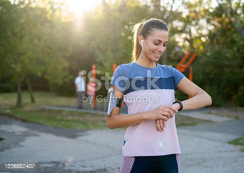 Portrait of a beautiful smiling young sportswoman resting after workout in public park. Young woman checking pulse on her smart watch.