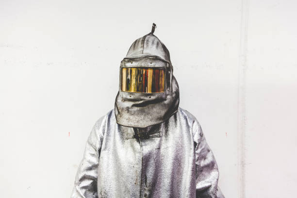 portrait of a steel worker in a silver suit with a fire mask stock photo