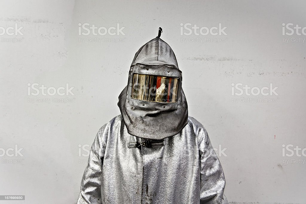 Portrait of a steel worker in a silver suit with a hood stock photo