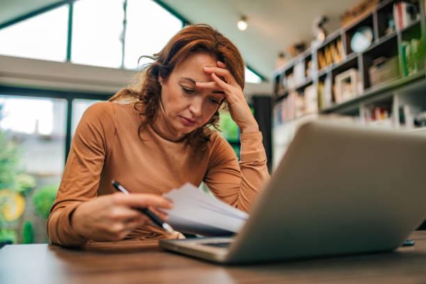 Retrato de una mujer estresada mirando facturas financieras, de cerca. - foto de stock