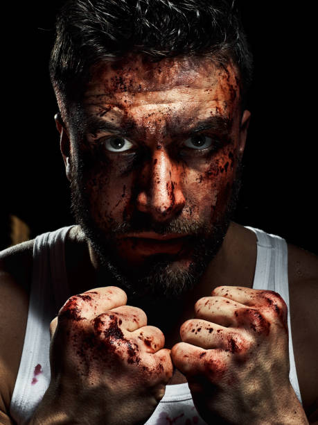 Portrait of a strong man with a beard, face in blood. stock photo