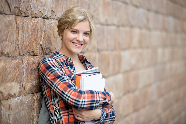 portrait of a student with books against the brick wall - wellness seminar stock-fotos und bilder