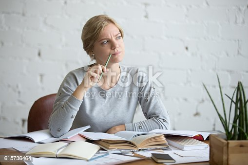 istock Portrait of a student woman at the desk, frowned 615736464