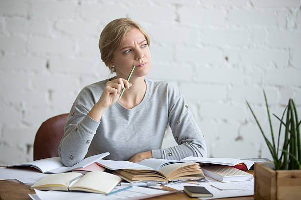 portrait of a student woman at the desk, frowned - reminder stock photos and pictures